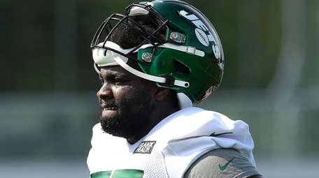 Mekhi Becton of the Jets looks on at