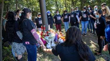 Family and friends of victims encircle a makeshift