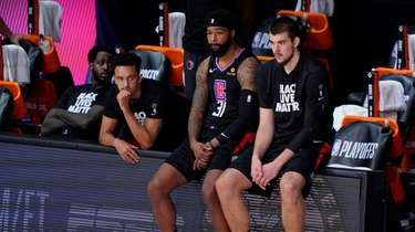 The Clippers players sit on the bench during