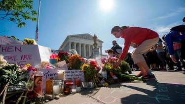People place flowers outside of the U.S. Supreme