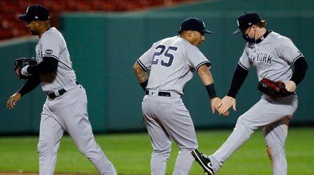 The Yankees' Aaron Hicks, left, Gleyber Torres and