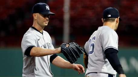 The Yankees' J.A. Happ, left, taps gloves with