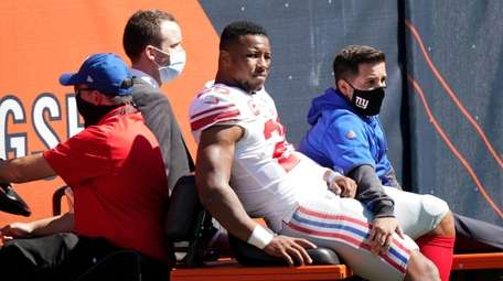 Giants running back Saquon Barkley (26) is carted