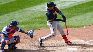 Atlanta's Travis d'Arnaud, right, hits a double against