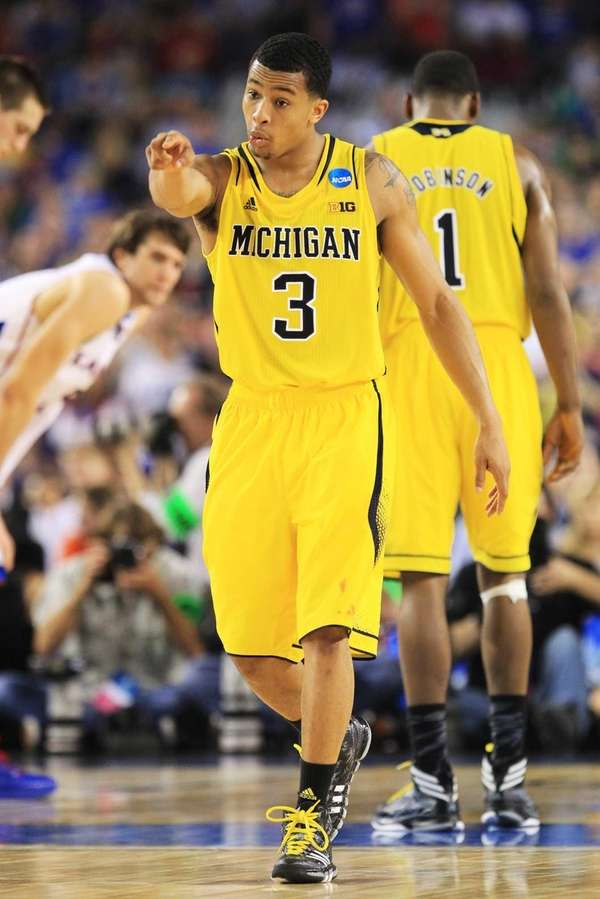 Trey Burke of the Michigan Wolverines celebrates during