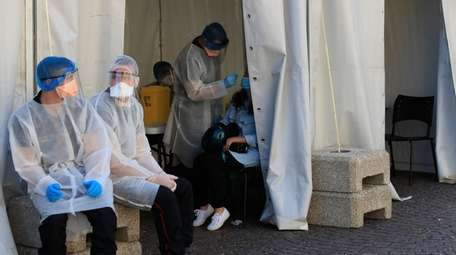 In Paris, firefighters collect nasal swab samples to