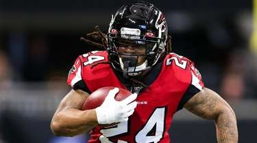 Devonta Freeman rushes at Mercedes-Benz Stadium on December