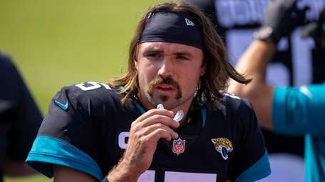 Jaguars quarterback Gardner Minshew walks in the bench