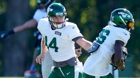 Jets quarterback Sam Darnold, left, hands off to