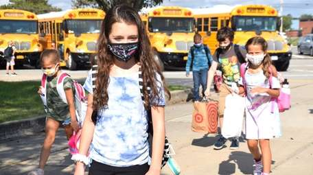 In Greenlawn, students wear masks as they return