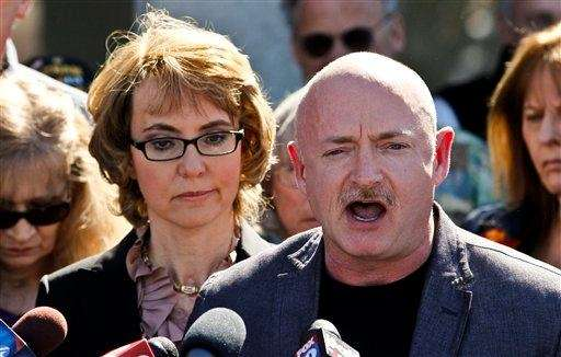 Former Rep. Gabrielle Giffords, left, listens to her