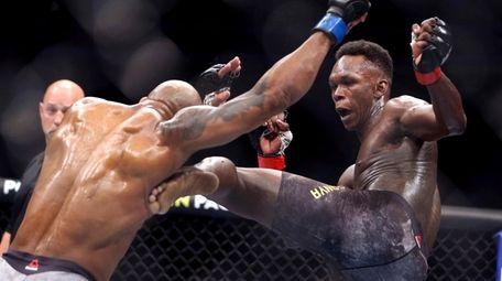 UFC middleweight champion Israel Adesanya, right, kicks challenger