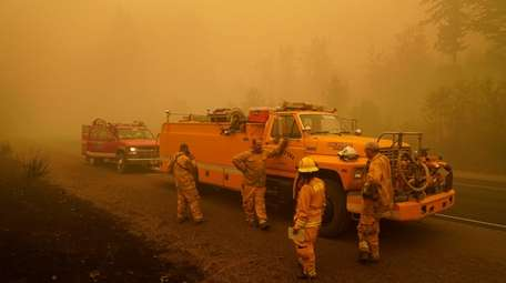 Firefighters wait alongside the road surrounded by smoke