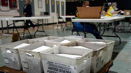 Workers prepare absentee ballots for mailing at the