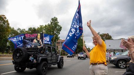 Trump supporter Karen Matthews waves a flag at