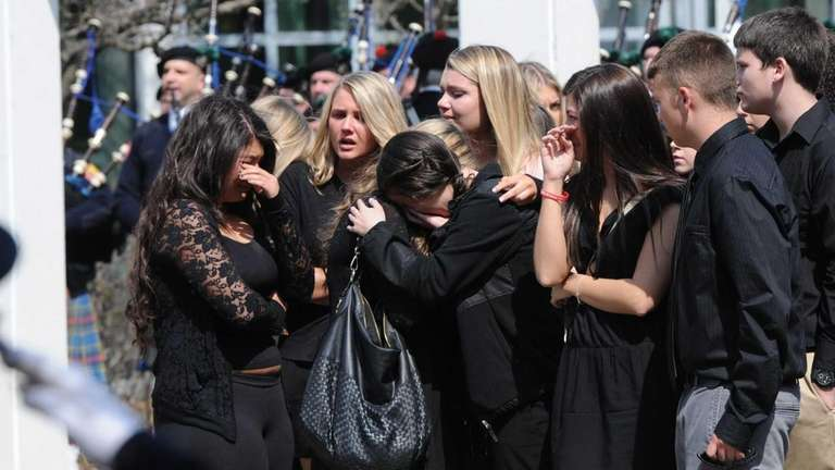 Friends of Liam Armstrong comfort each other outside