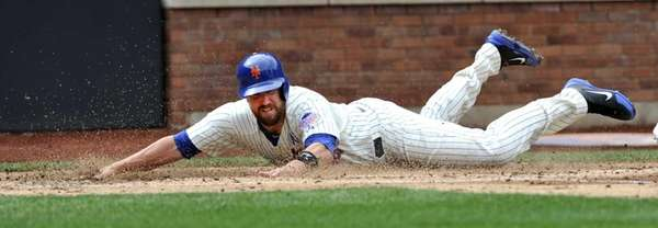 John Buck slides across home plate to score