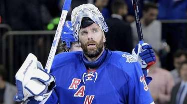 Rangers goalie Henrik Lundqvist raises his stick to