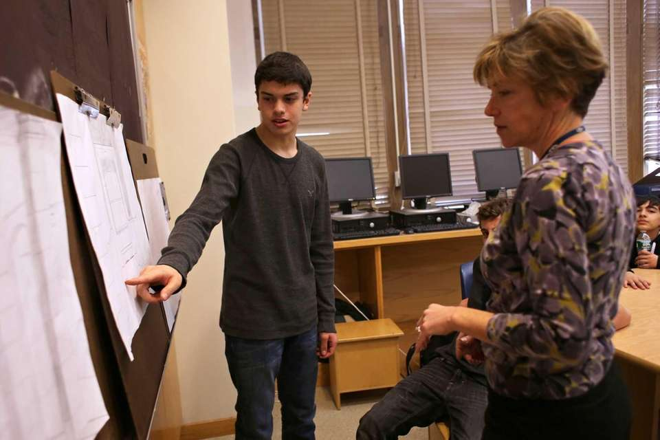 Chris Martin, 15, explains his architectural drawing during