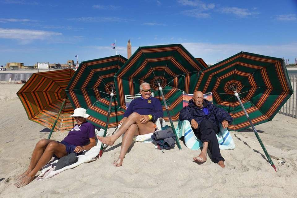 Lifeguard Cory Duryea, 70, of N.J., center, watches