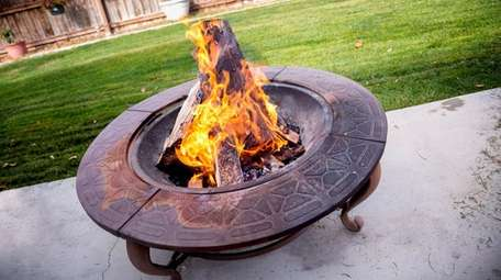 A portable fire pit burning in a backyard
