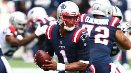 Cam Newton of the Patriots looks to hand