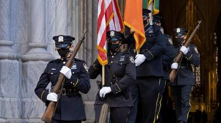 An NYPD honor guard leaves St. Patrick's Cathedral