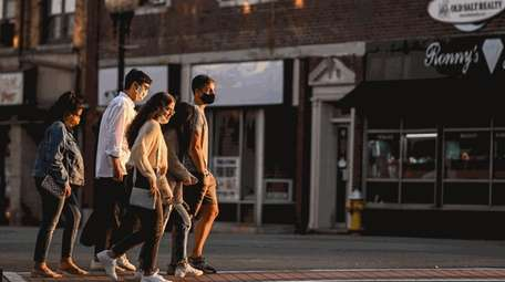 Pedestrians make their way through downtown Patchogue.