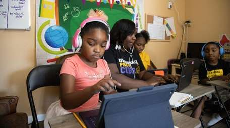 Ebony Guerrier works with her children Madison, 6,