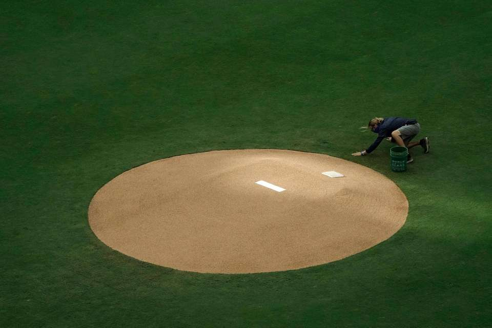 A member of the grounds crew smooths a