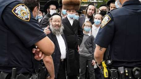 Jewish Orthodox community members speak with NYPD officers