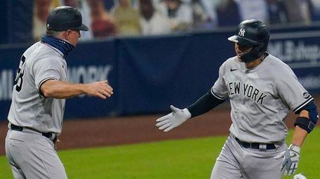 Yankees catcher Kyle Higashioka is congratulated by third