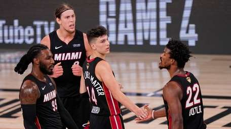 The Heat's Tyler Herro, center, high-fives Jimmy Butler