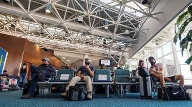 Passengers wearing protective masks wait for flights at