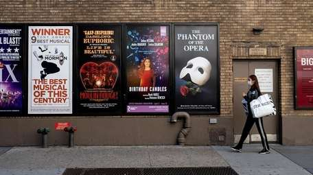 A pedestrian passes the posters of shuttered Broadway