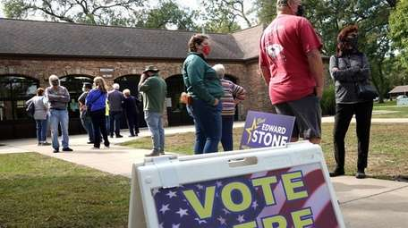 Residents wait in line to vote at the