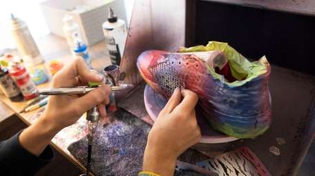 Anthony DeLucia painting cleats with an air brush.