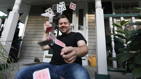 "Thomas Joseph Tana performs a ""card spring"" outside"