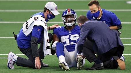 Lorenzo Carter (59) of the Giants is tended
