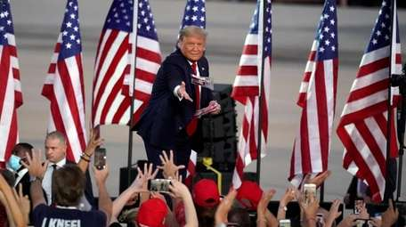 President Donald Trump tosses items to supporters at
