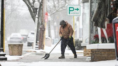 Juan Saenz, of Brentwood, shovels a walkway in