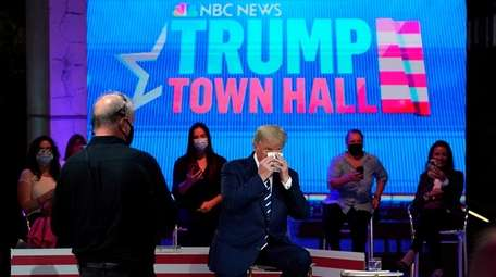 President Donald Trump wipes his face during a