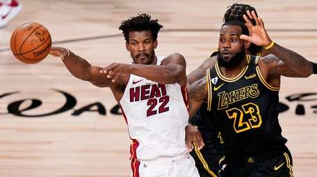 Heat forward Jimmy Butler, left, passes around Lakers