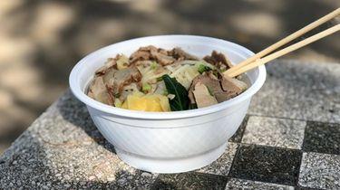 A bowl of pork noodle soup with wontons