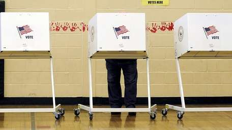 A voter in a booth on Election Day,