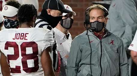 A masked Alabama coach Nick Saban speaks with