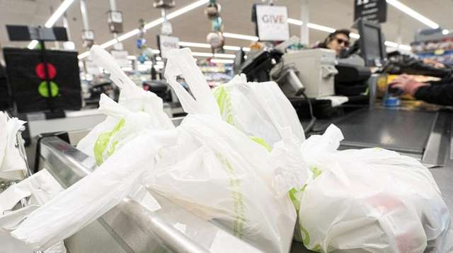 A customer's groceries are held in plastic bags