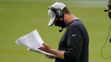 Jets head coach Adam Gase looks at copies