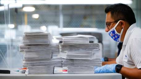 Stacks of ballots are prepared to be checked
