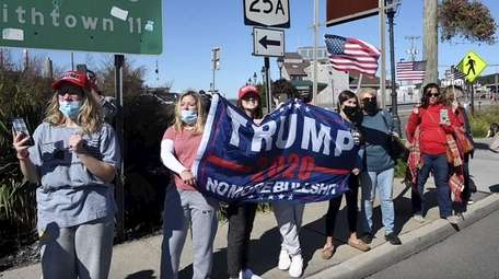 Trump supporters greet a truck and car parade